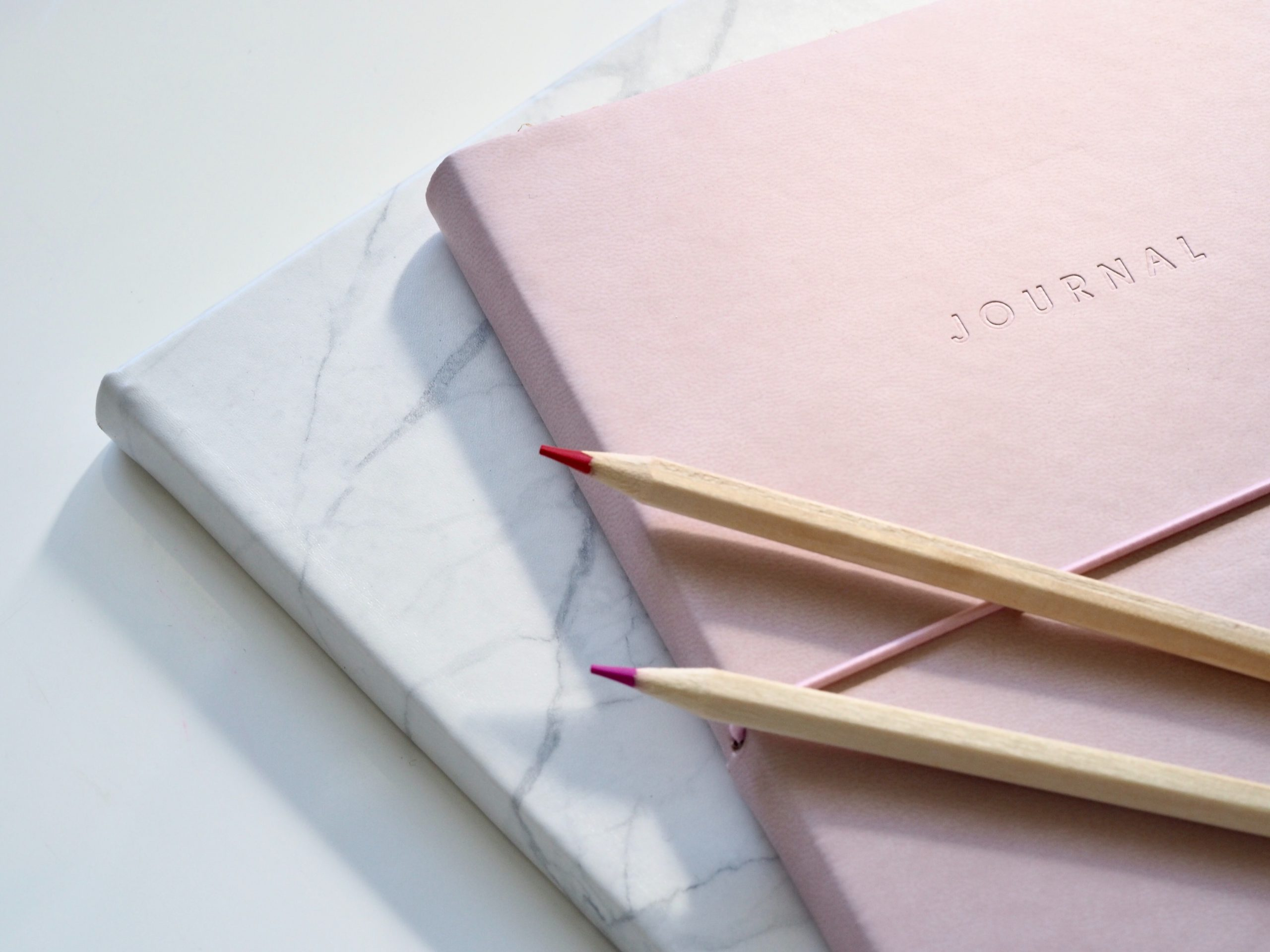 light pink journal and two pencils on a white background